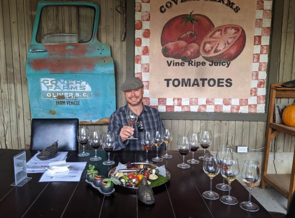 JR sat at table with two sets of seven glasses of wine and charcuterie plate, in front of Covert Farms art