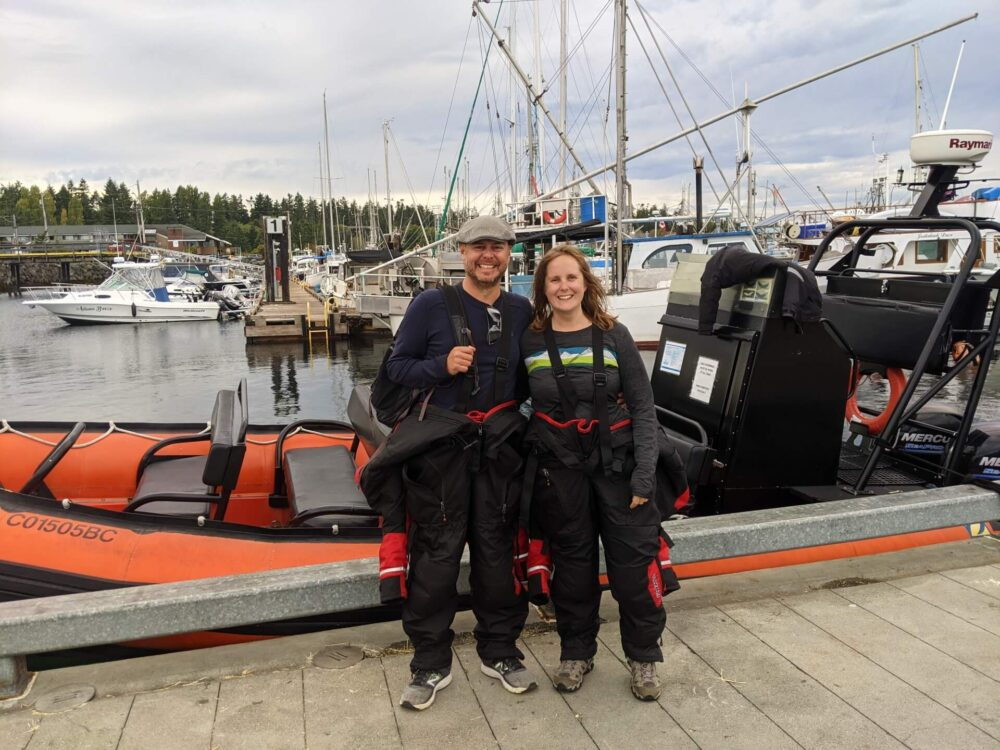 Front view of JR and Gemma in front of whale watching zodiac boat in Parksville. Both are wearing floatation suits