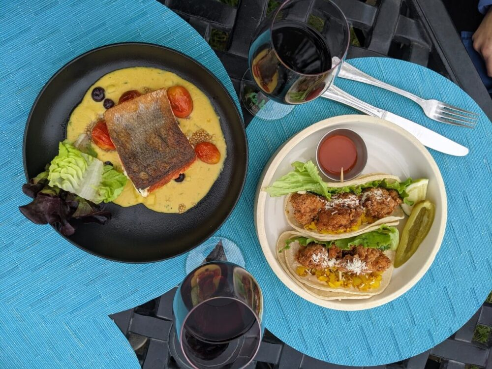 Overhead view of two plates and two glasses of wine at Nk'Mip Cellars, with one salmon dish and one chicken taco dish