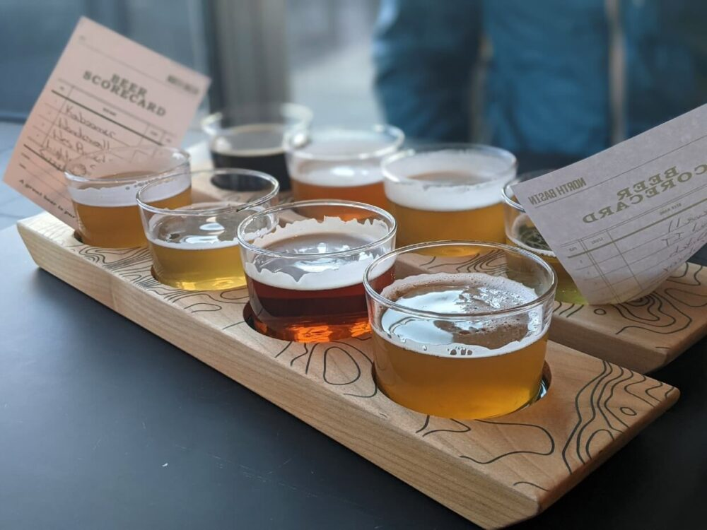 Close up of two flights of beer, with eight total glasses, each with a differently coloured beer