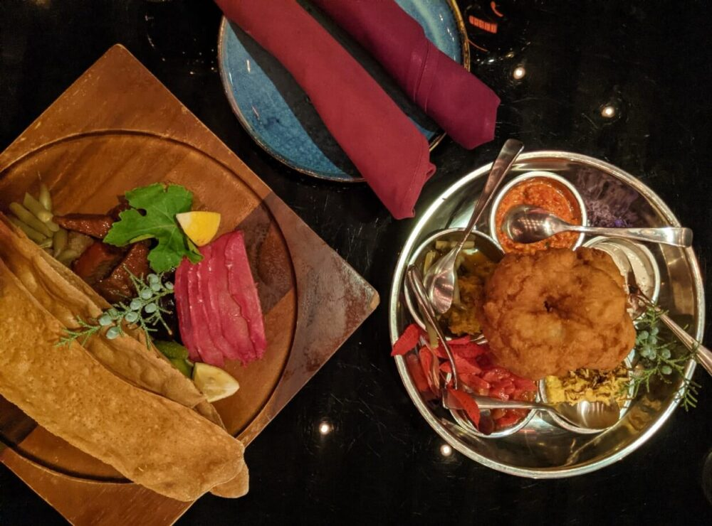 Overhead view of shared dishes at The Bear, the Fish, the Root & The Berry, with plate and napkins