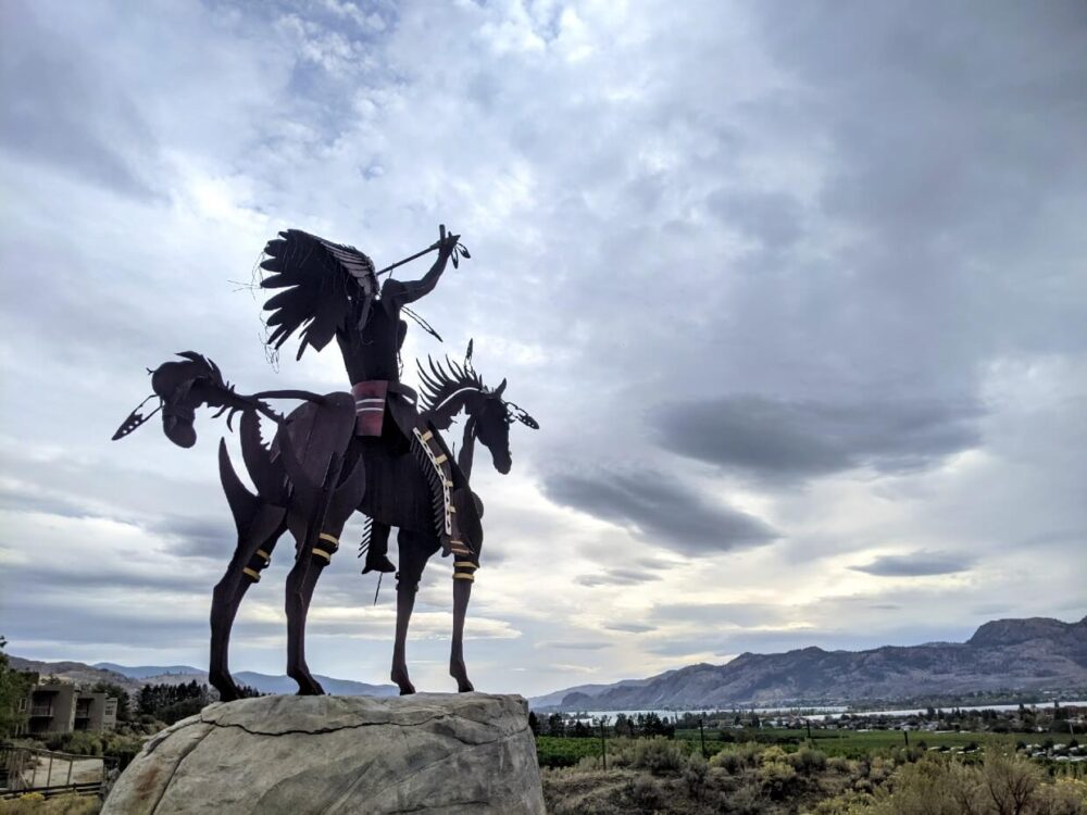 Back view of metal Indigenous statue at Spirit Ridge, with a man on a horse looking at sky