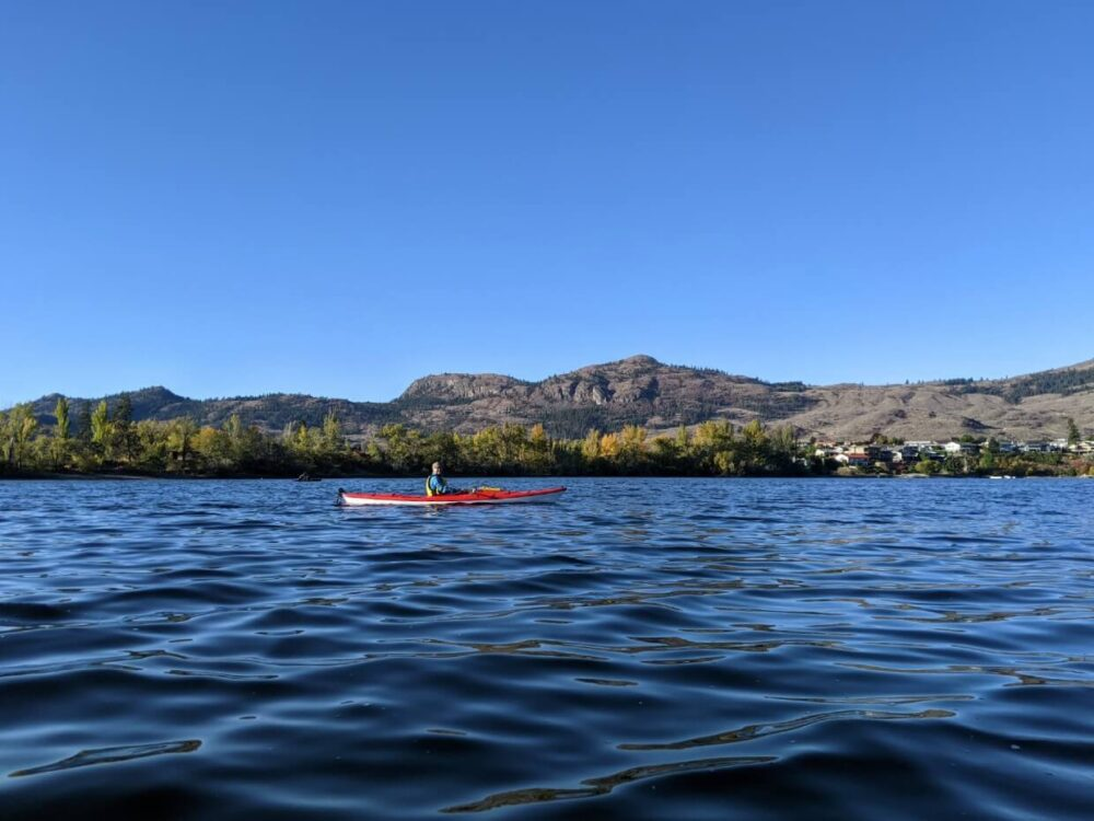 Kayak view of red kayak on Osoyoos Lake, with yellow coloured trees lining shore in background