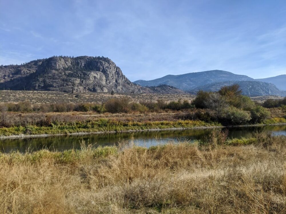 View looking across canal towards rugged desert and rugged hill scenery on Oxbows Trail