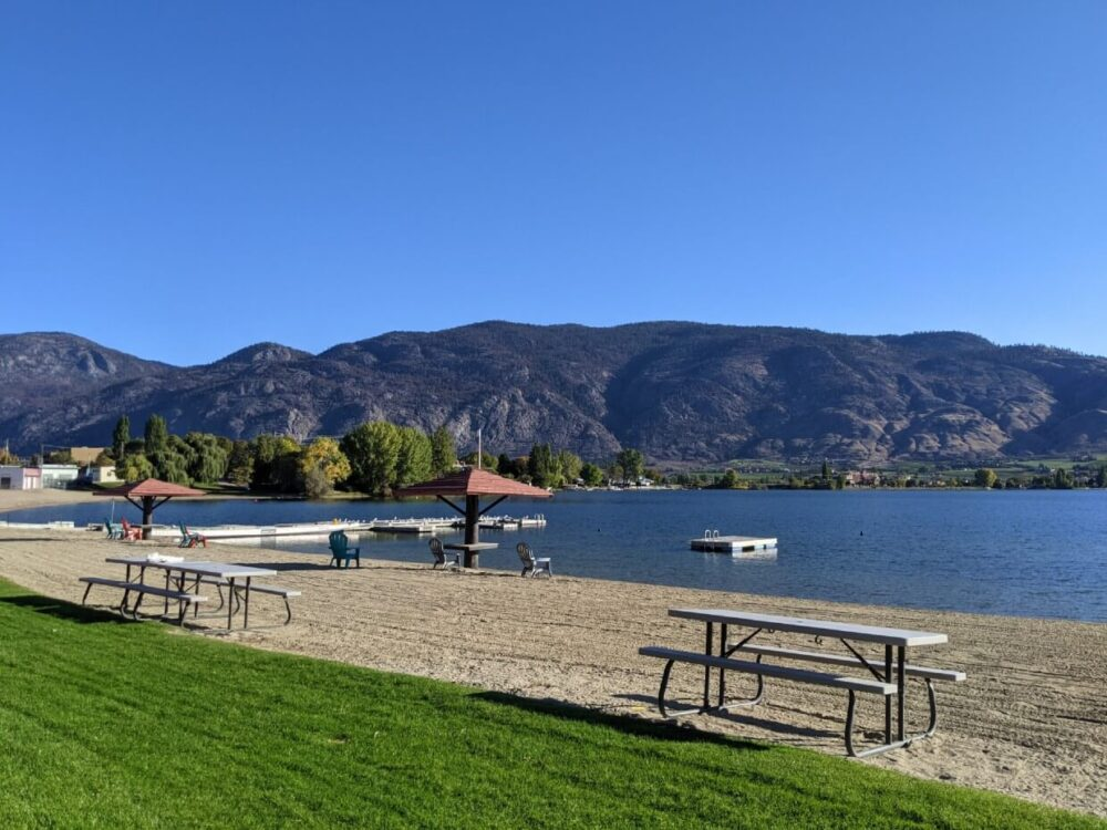 Side view of on beach and lawn space, with picnic tables and Adirondack chairs, next to calm blue lake and surrounding hills