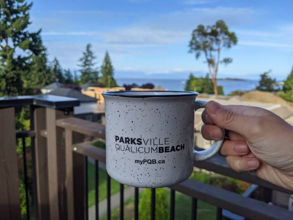 Close up of white Parksville Qualicum Beach mug in front of sunny ocean view at Sunrise Ridge Waterfront Resort